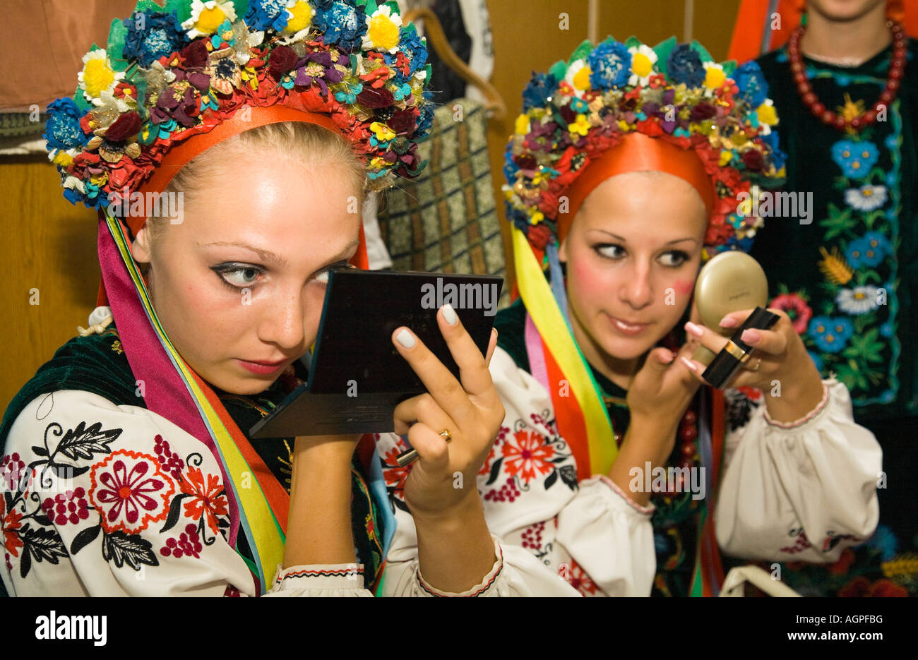 Two members of the folk dance group Bessarabskij Souvenir are busy with their make up before a performance - Stock Image
