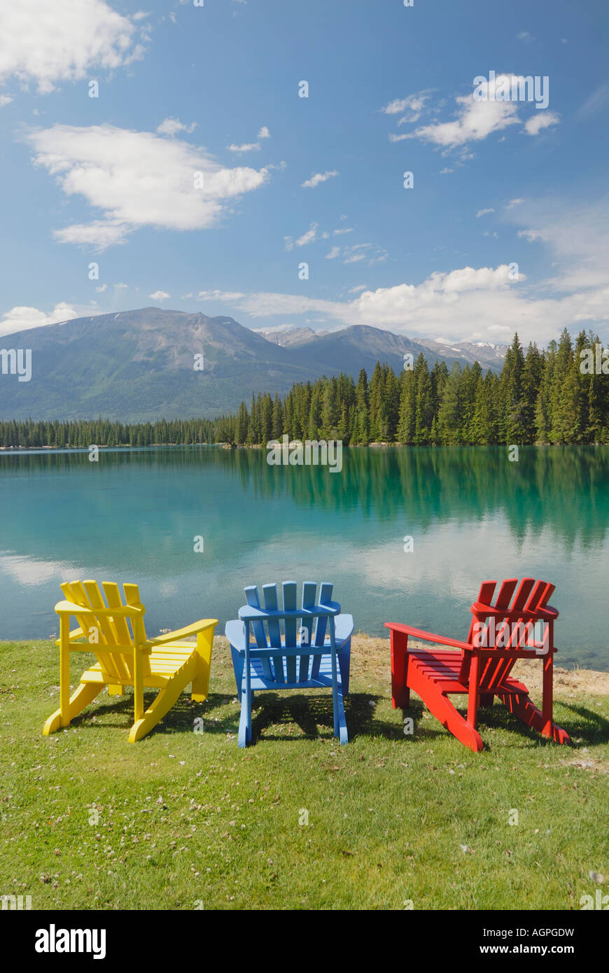 View of Adirondack lounge chairs in front of Lake Beauvert at Fairmont Jasper Park Lodge in Alberta Canada - Stock Image