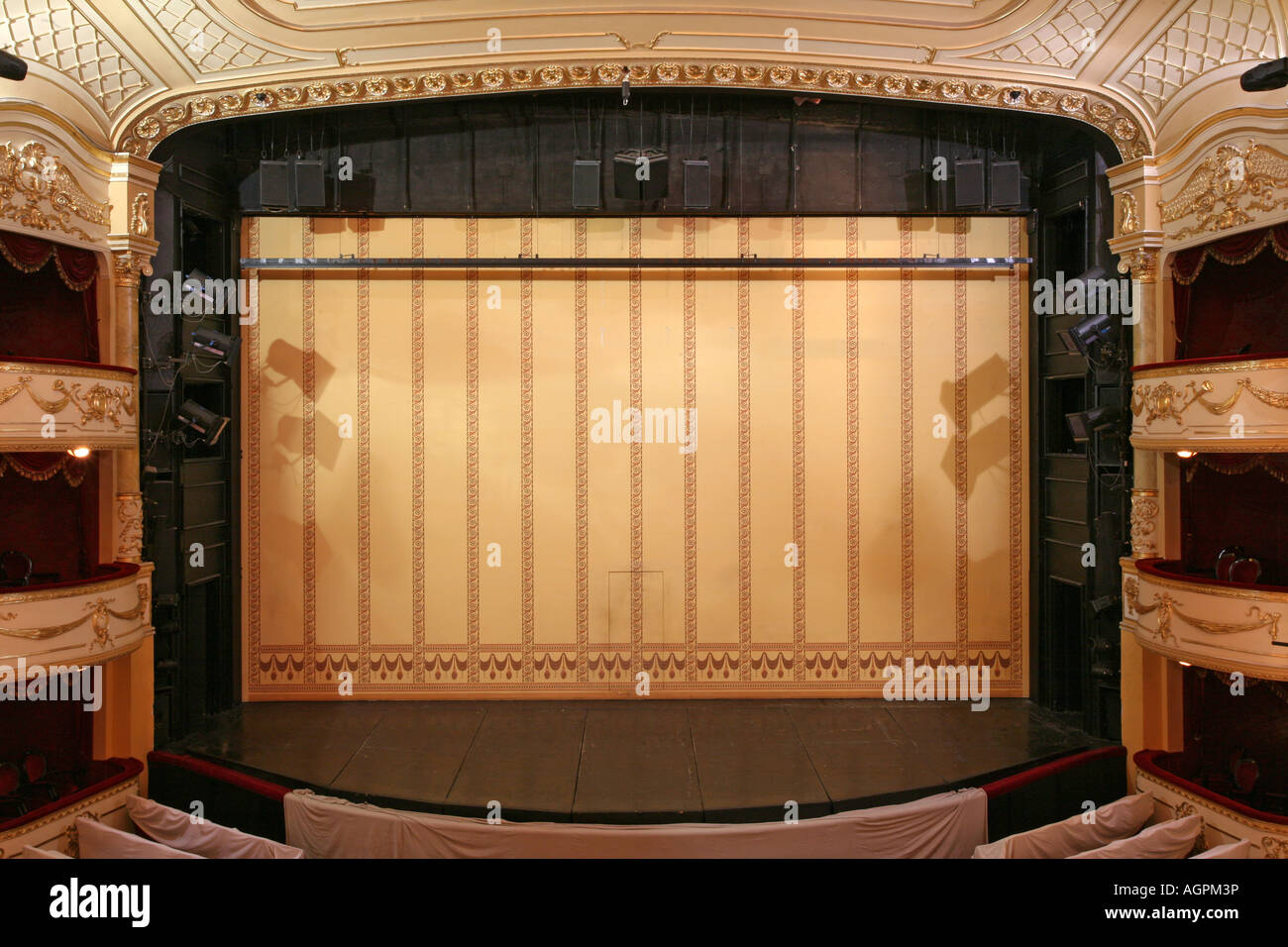 Theater stage with gold safety curtains and empty chairs in the ...