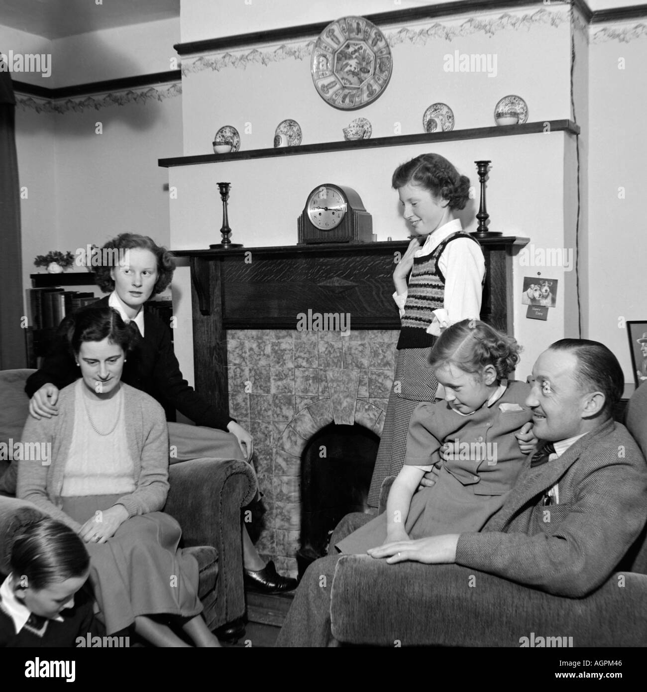 OLD VINTAGE BLACK AND WHITE FAMILY SNAPSHOT PHOTOGRAPH OF MOTHER FATHER AND FOUR CHILDREN RELAXING IN LIVING ROOM OF HOUSE 1950 - Stock Image