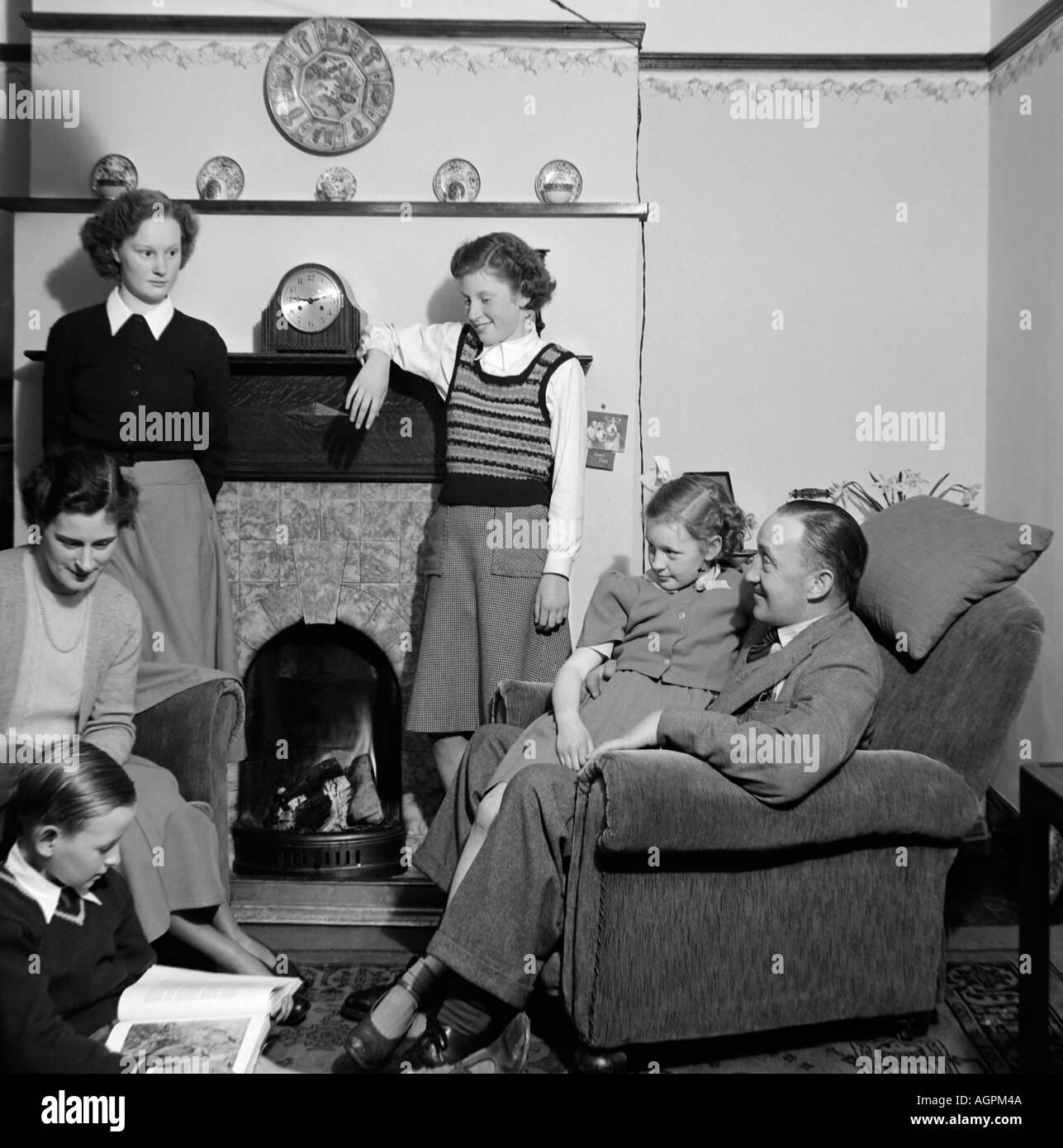 OLD VINTAGE FAMILY SNAPSHOT PHOTOGRAPH OF  MOTHER FATHER AND FOUR CHILDREN RELAXING IN LIVING ROOM OF HOUSE 1950 - Stock Image