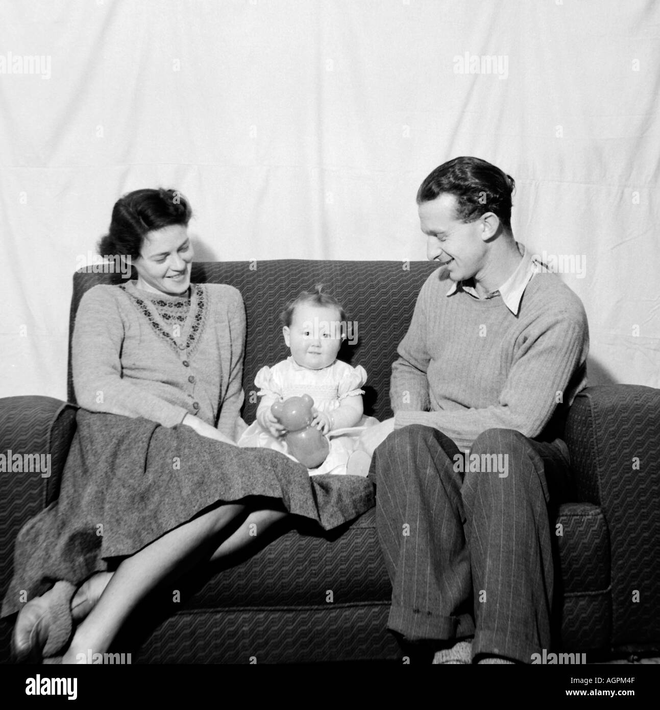 OLD VINTAGE FAMILY SNAPSHOT PHOTOGRAPH OF MOTHER AND FATHER RELAXING AND PLAYING WITH BABY DAUGHTER ON SOFA - Stock Image