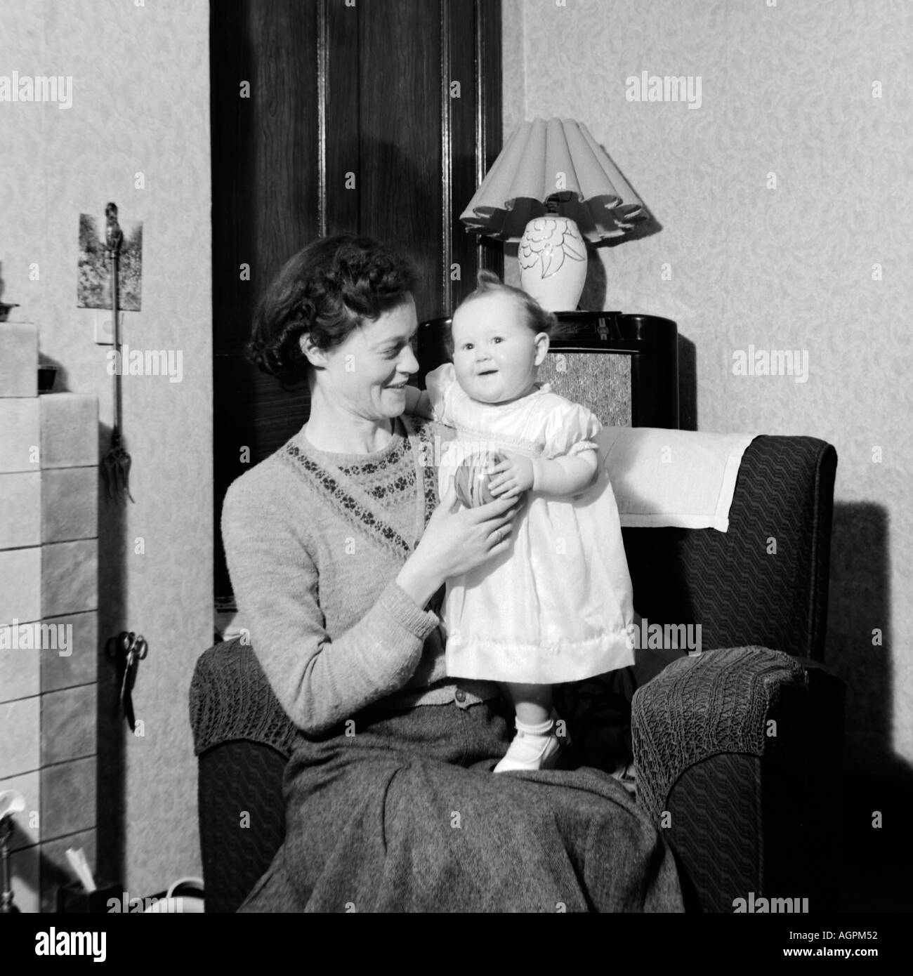OLD VINTAGE FAMILY SNAPSHOT PHOTOGRAPH OF MOTHER RELAXING AND PLAYING WITH BABY DAUGHTER - Stock Image