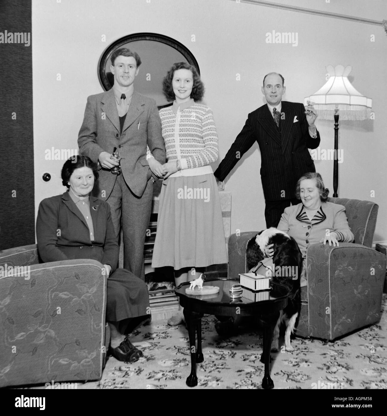 Old vintage black and white family snapshot photograph of group in living room circa 1950