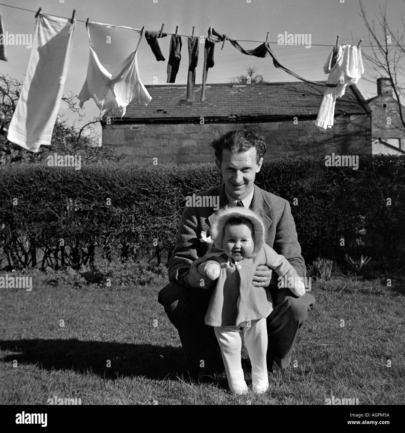 OLD VINTAGE FAMILY SNAPSHOT PHOTOGRAPH OF FATHER PLAYING WITH BABY DAUGHTER IN GARDEN OF HOME WITH WASHING LINE IN BACKGROUND CI - Stock Image