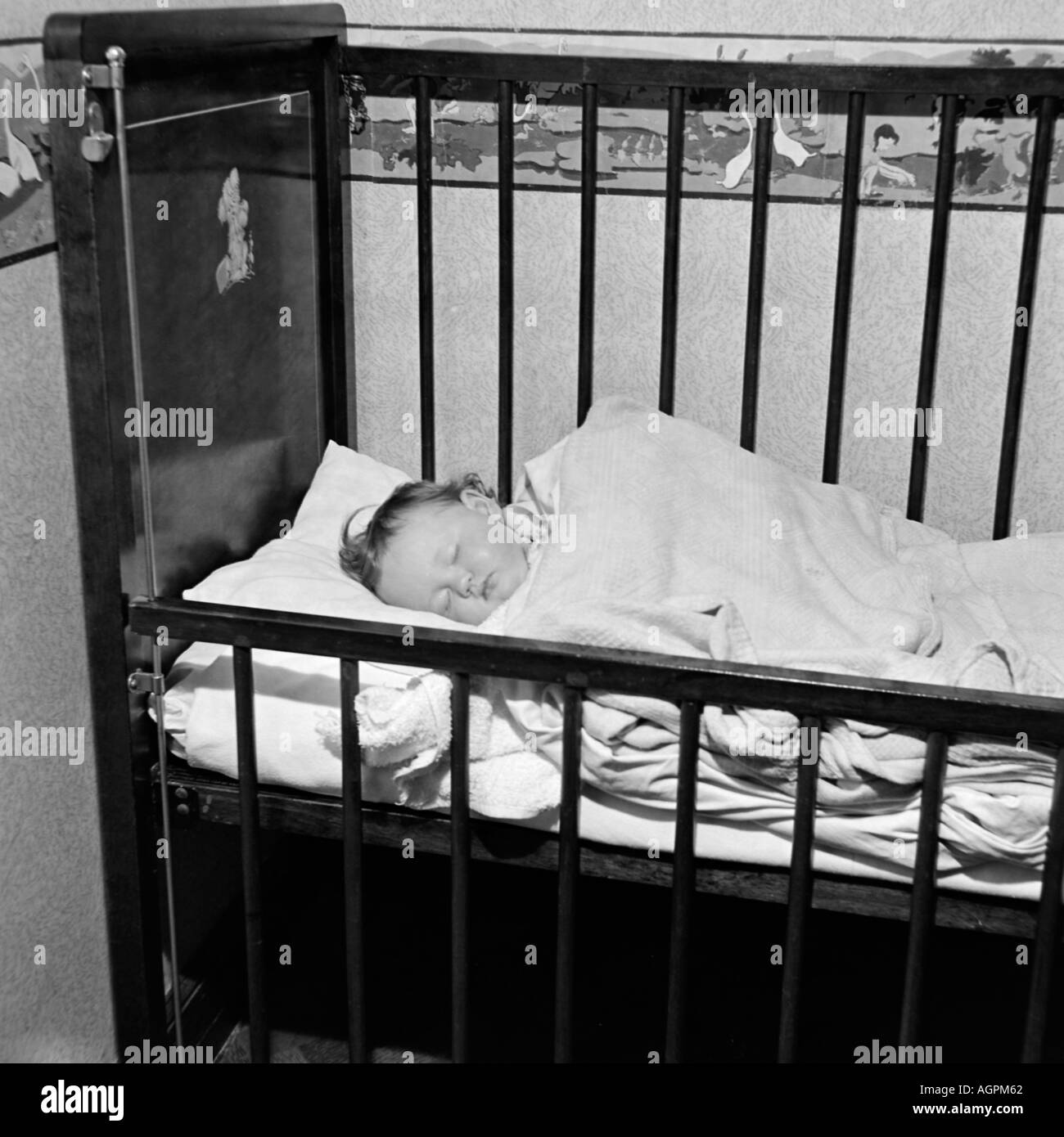 OLD VINTAGE FAMILY PHOTOGRAPH SNAP SHOT BABY GIRL SLEEPING IN NURSERY COT Stock Photo