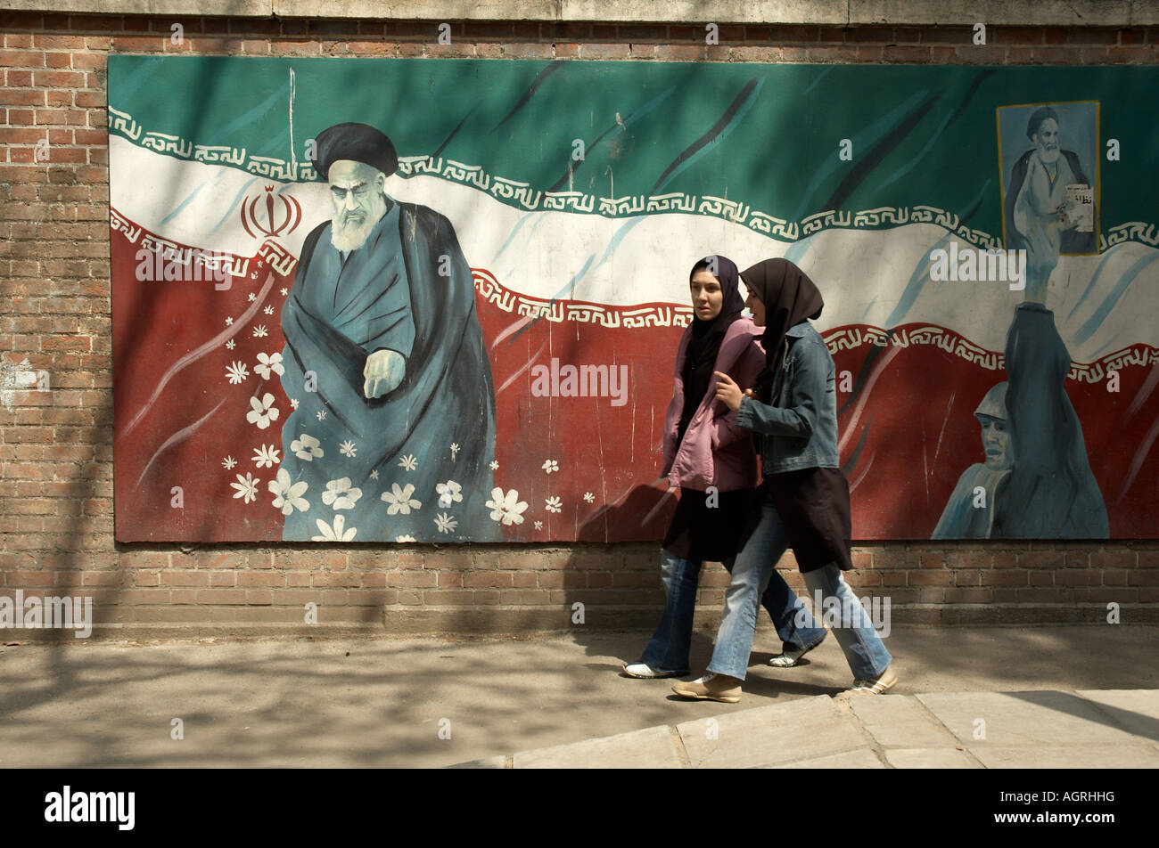 Two woman wearing Islamic uniforms walking in front of the painting of Ayatollah Khomeini and the Iranian flag on - Stock Image