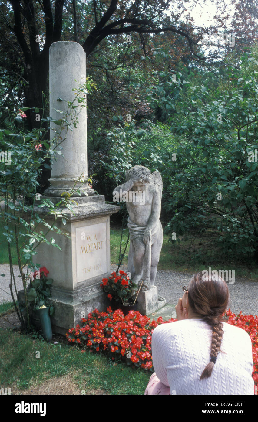 Woman sitting at the gravestone of Wolfgang Amadeus Mozart at the Sankt Marx cemetery in Vienna Austria - Stock Image