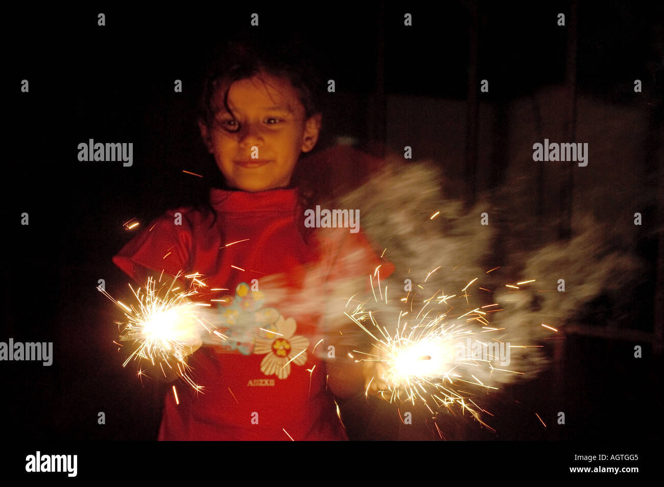 HMA79955 Indian girl holding two burning brightly sparklers fire cracker in her hands on Diwali Festival of lights Stock Photo
