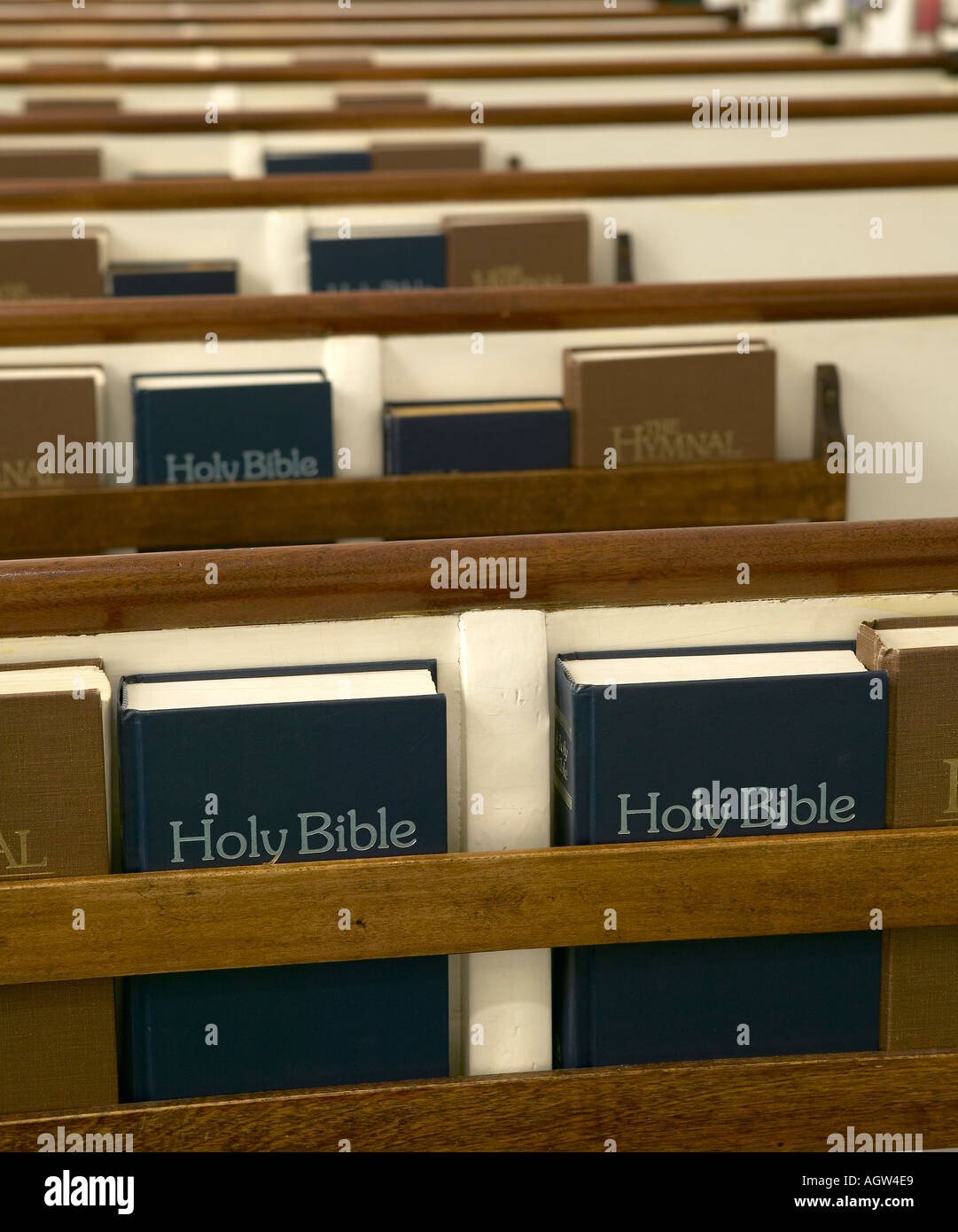 Holy Bibles and Hymnals stored in church pews - Stock Image