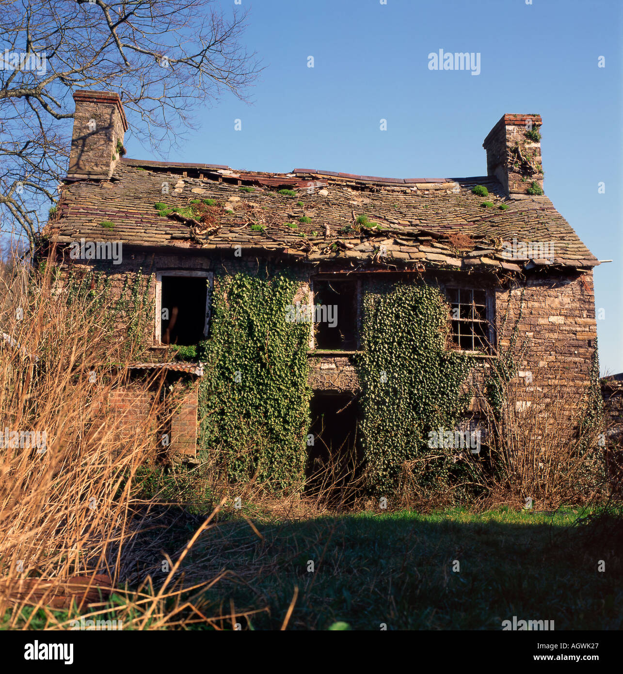 Derelict abandoned old stone house cottage with loose roof tiles Wales, UK KATHY DEWITT Stock Photo