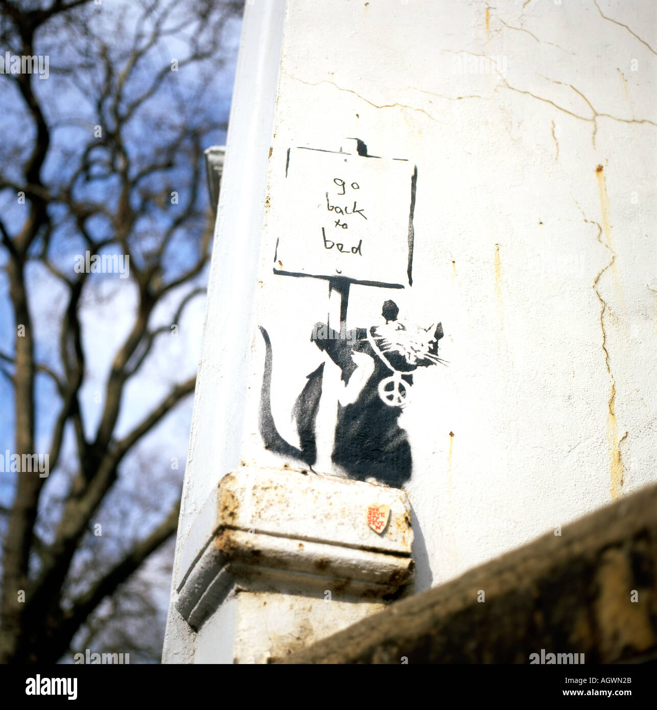 Banksy graffiti of a rat holding a 'Go Back To Bed' sign in Clerkenwell, London England UK  KATHY DEWITT - Stock Image