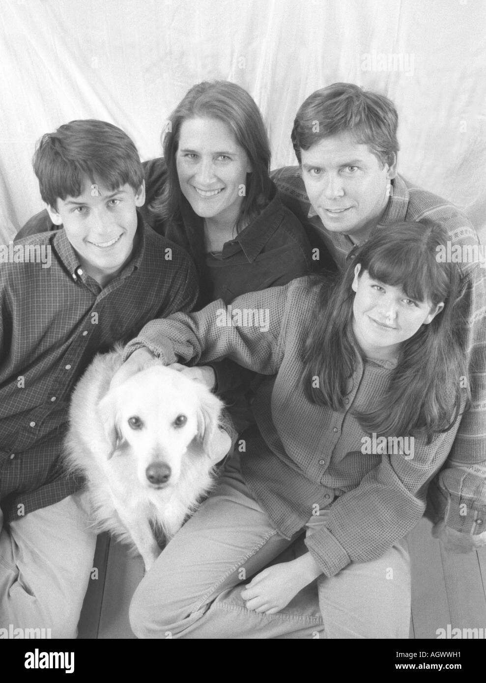 Black and white group photo of a seated Caucasian family of four with their dog: Mother, Father, and preteen son and daughter. - Stock Image