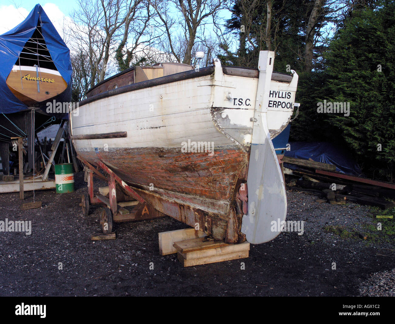 Wooden boat in boatyard for repainting - Stock Image