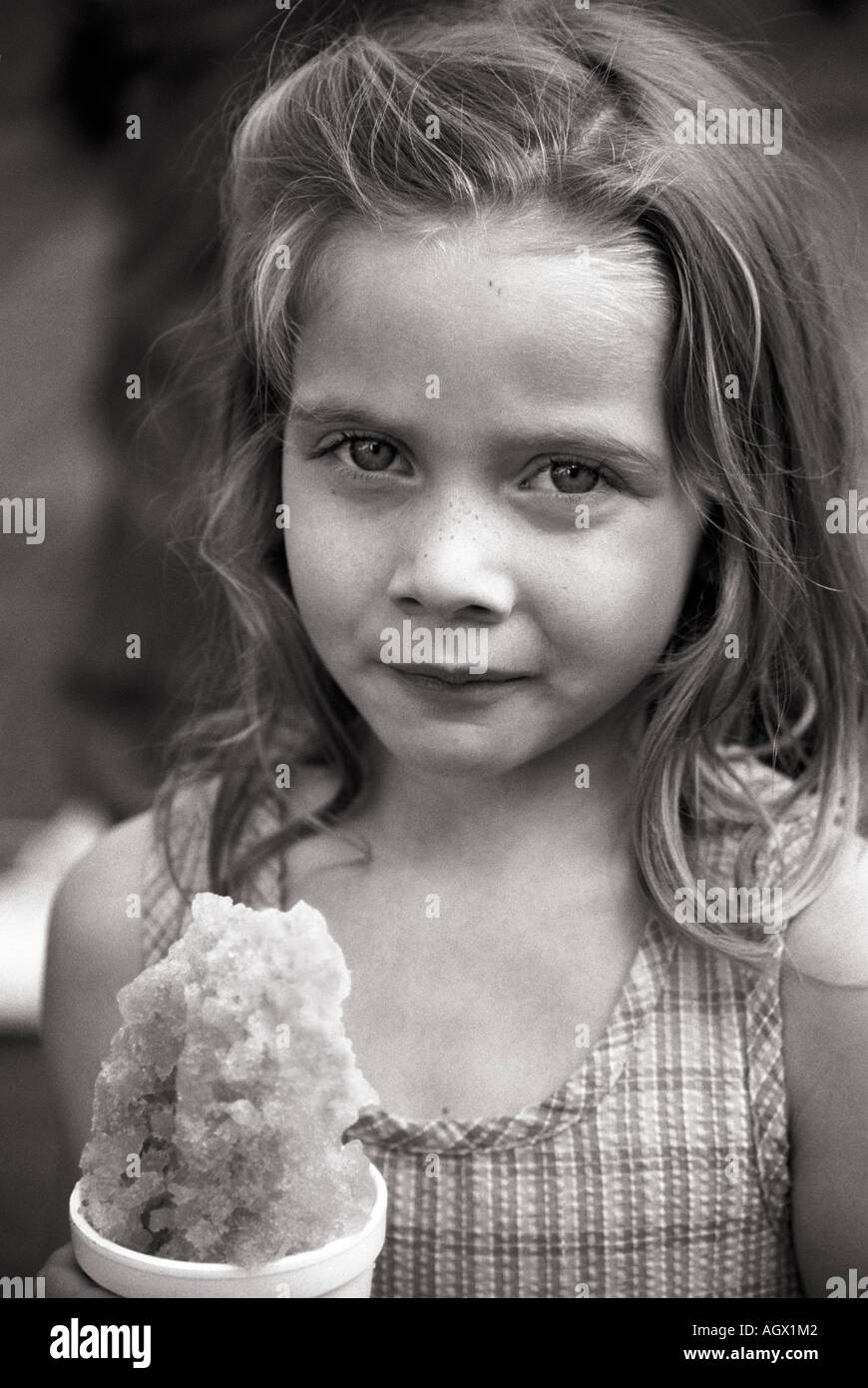 girl holding a snow cone on a summer day. - Stock Image