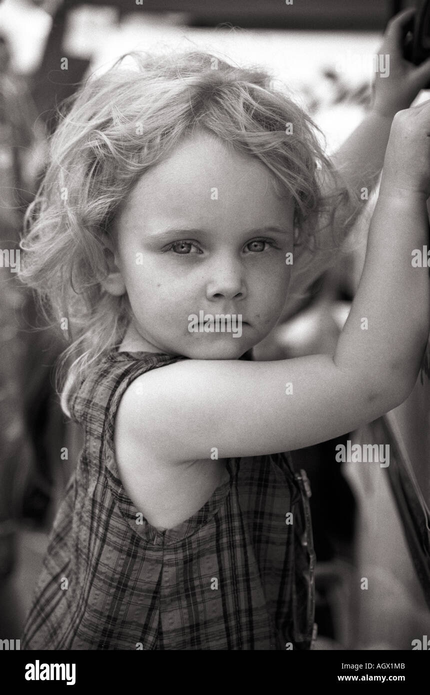 little girl holding onto the edge of an ice cream trailer - waiting. - Stock Image