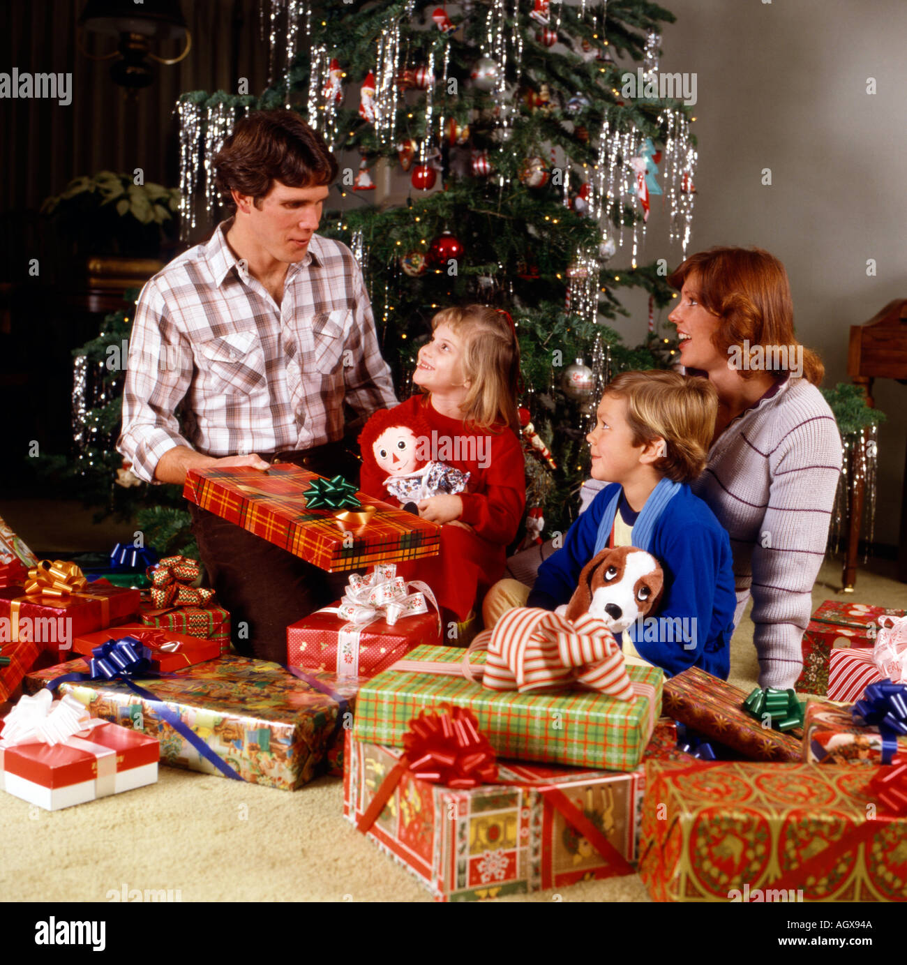 family exchanging christmas presents in front of their tree on christmas day stock image