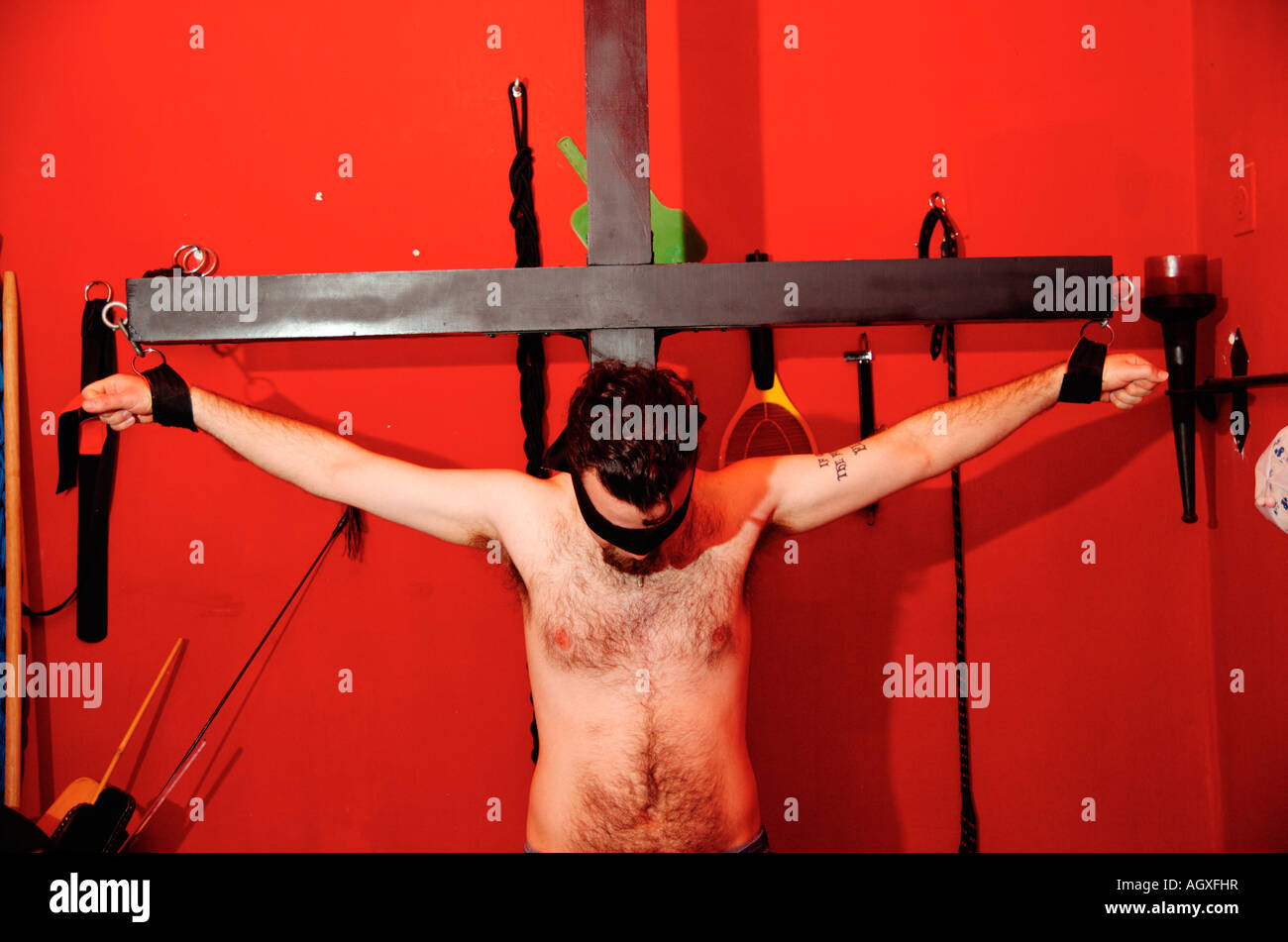 Bdsm Dungeon crucified blindfolded young man in a bdsm dungeon stock