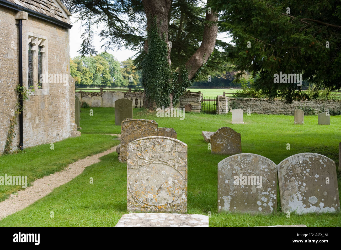 The churchyard of St Peters church in the Cotswold village of Ampney St Peter, Gloucestershire - Stock Image