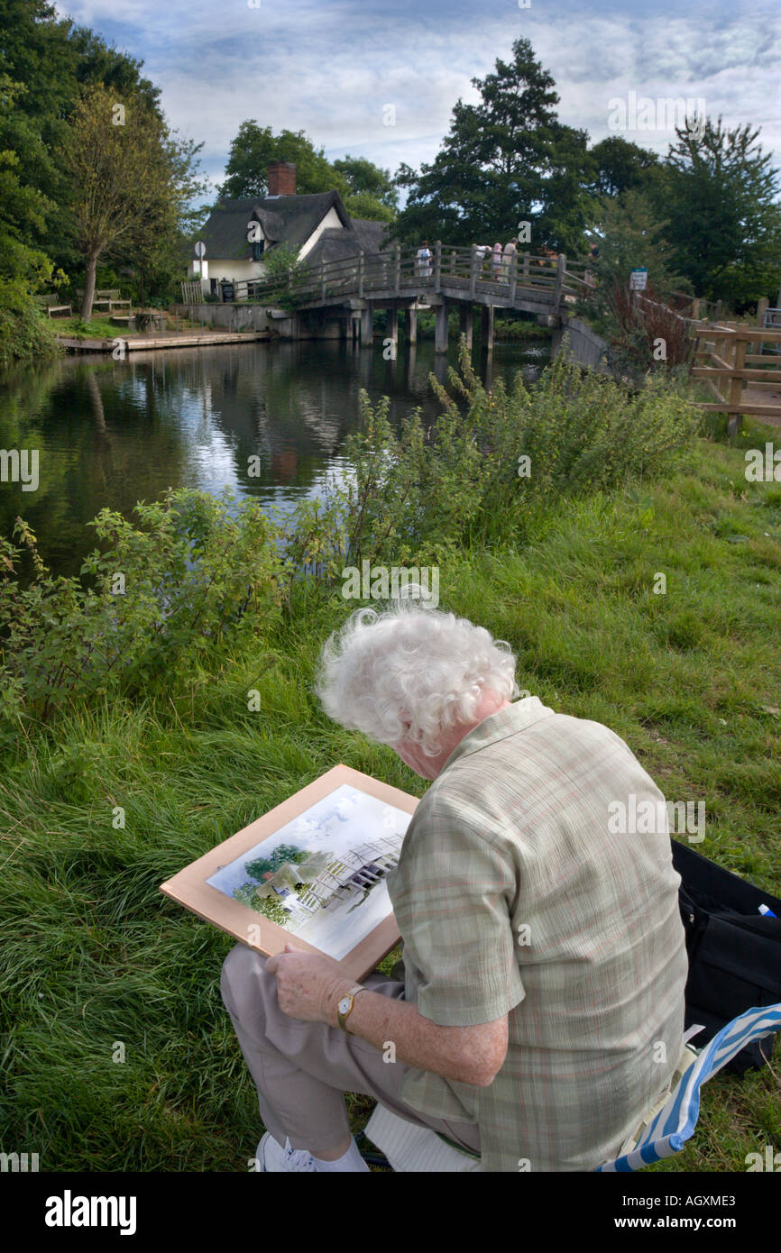 A painter doing a watercolour of the Bridge Cottage at Historic Flatford in Suffolk England Stock Photo