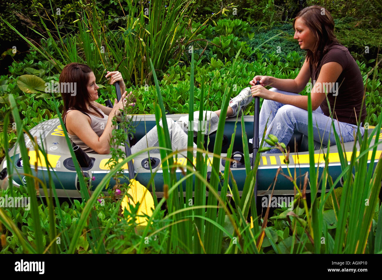 summertime.Two pretty girls in dingy alongside reeds.etc. - Stock Image