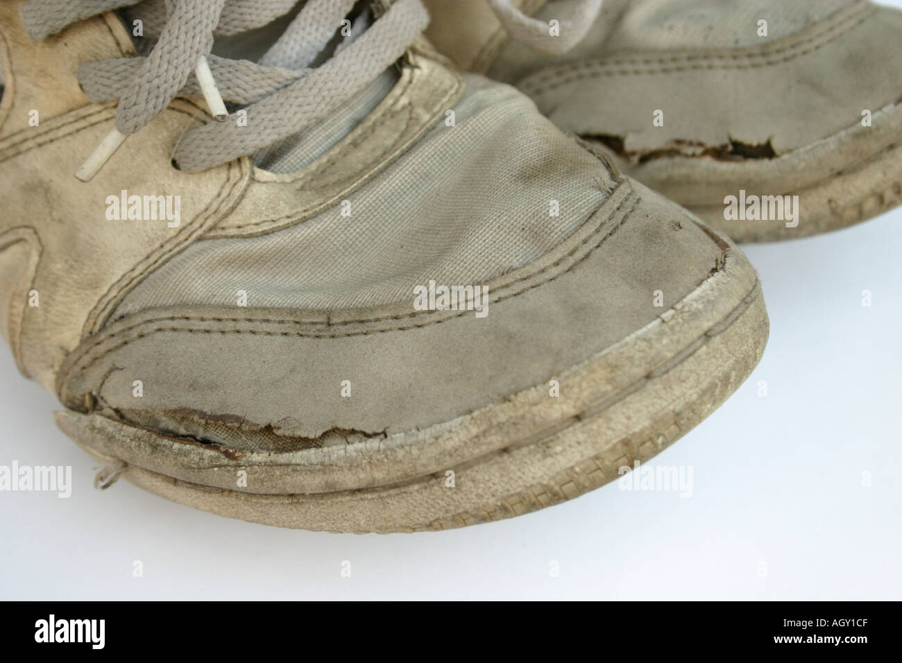 closeup of a pair of dirty old worn sneakers - Stock Image