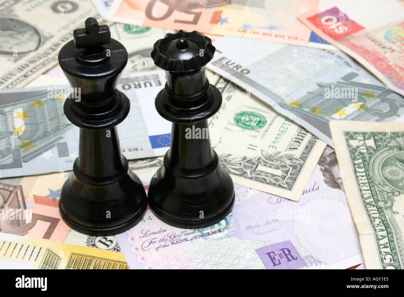 king and queen sitting on cash rich couple - Stock Image
