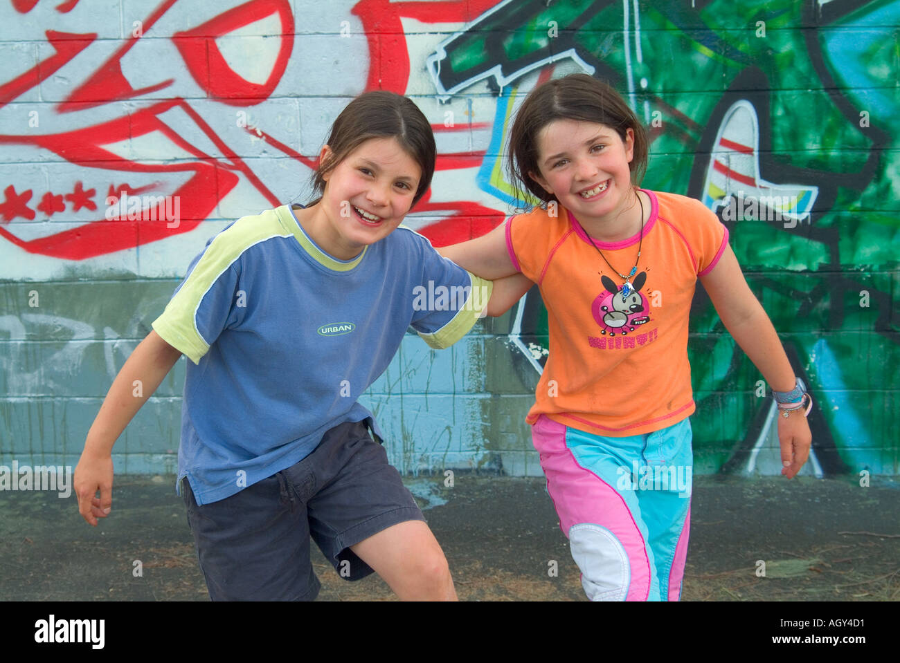 Two pre teen friends against a wall of graffiti - Stock Image