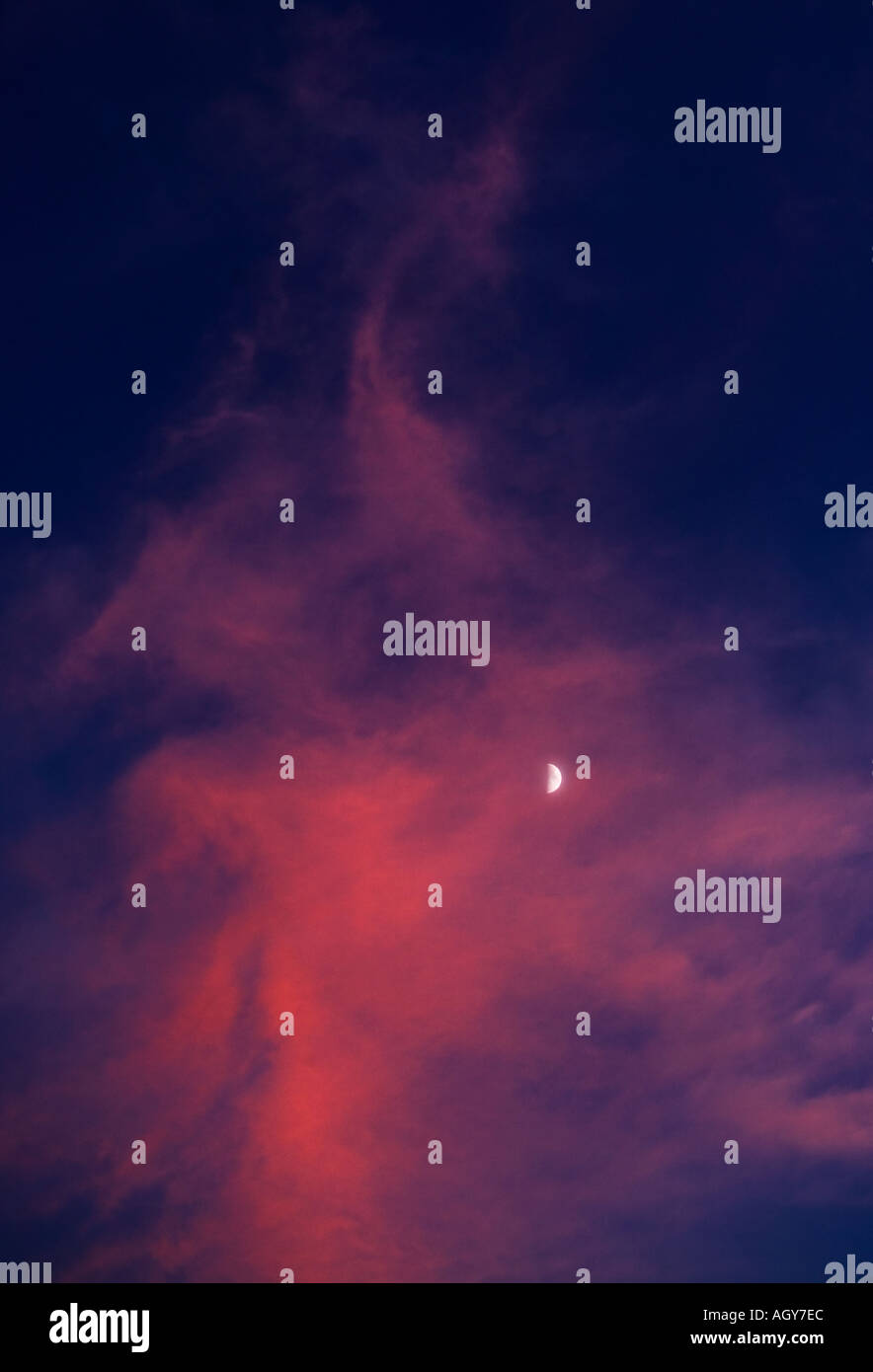 Moon peaks through sunset clouds during twilight hours - Stock Image