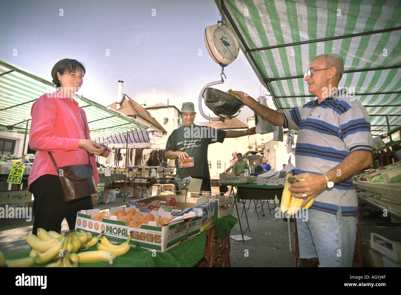 THE HAMPSHIRE TOWN OF ROMSEY UK TRADER JIMMY SULLIVAN SERVES A CUSTOMER FROM HIS FRUIT AND VEG STALL IN THE DOLPHIN MARKET - Stock Image