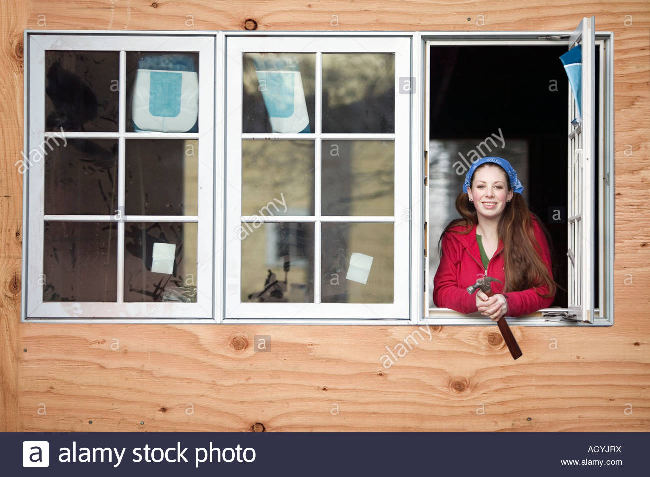 Woman looking out construction site window - Stock Image