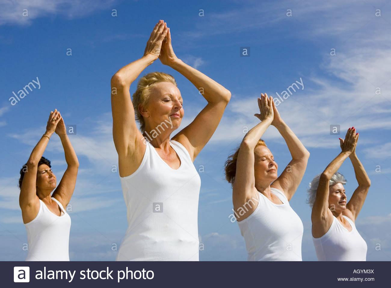 Group of senior women exercising under blue sky - Stock Image