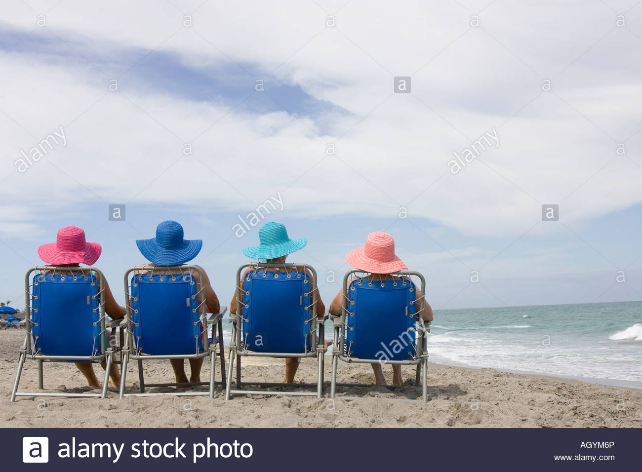 Rear view of four women in beach chairs - Stock Image
