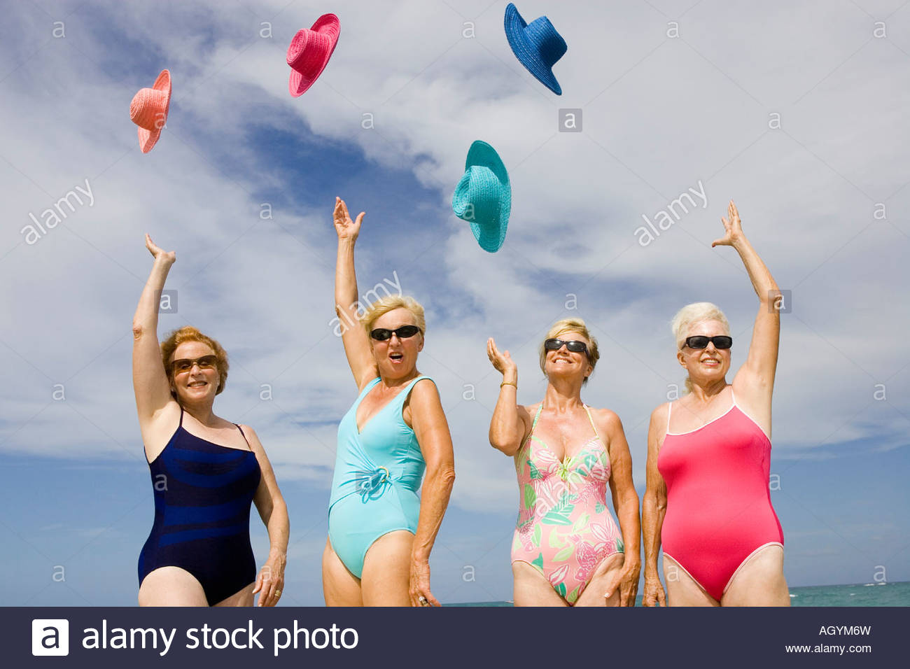 Group of senior women in bathing suits tossing hats in air - Stock Image