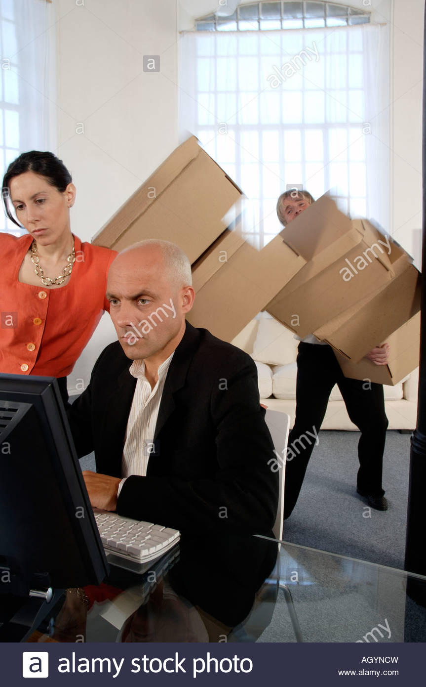 Businessman working while co-worker drops moving boxes - Stock Image