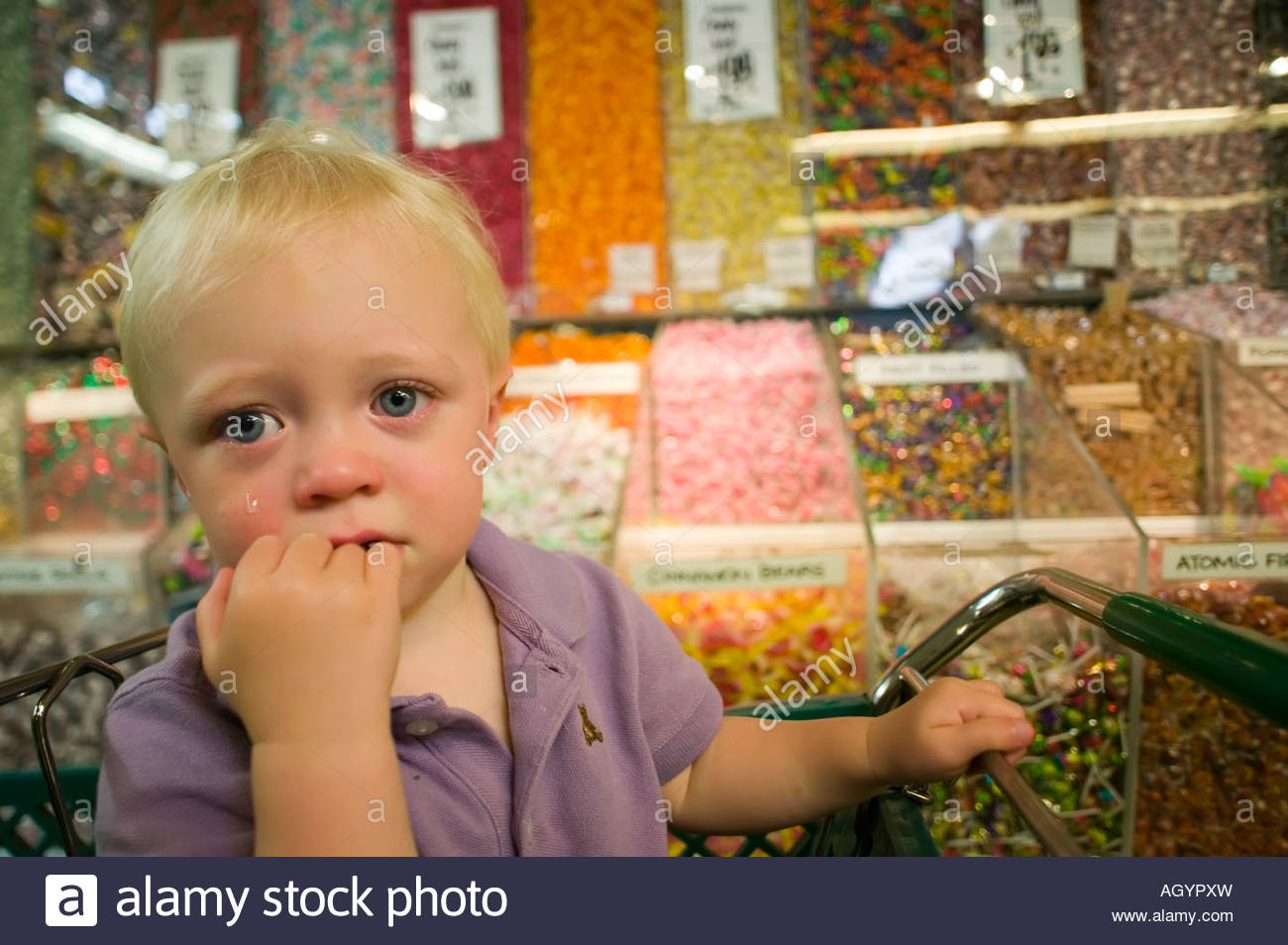 Toddler boy crying in candy aisle of grocery store - Stock Image