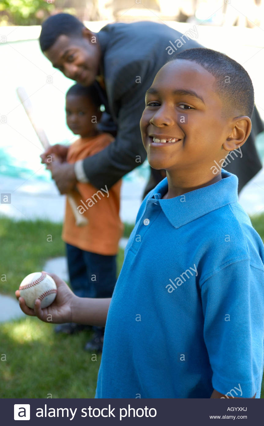 African boy playing baseball with family  - Stock Image