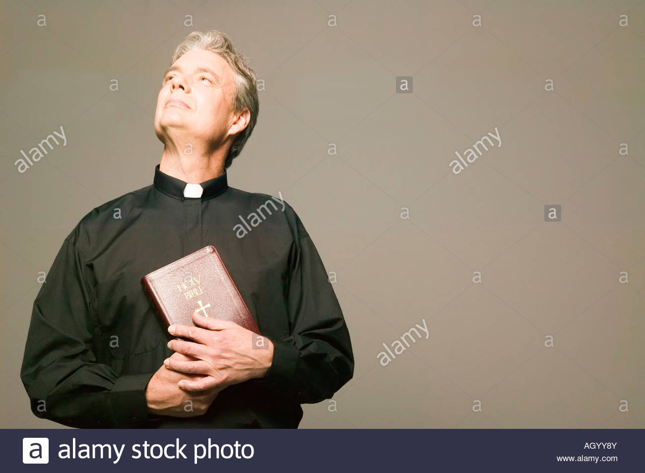 Priest holding Bible - Stock Image