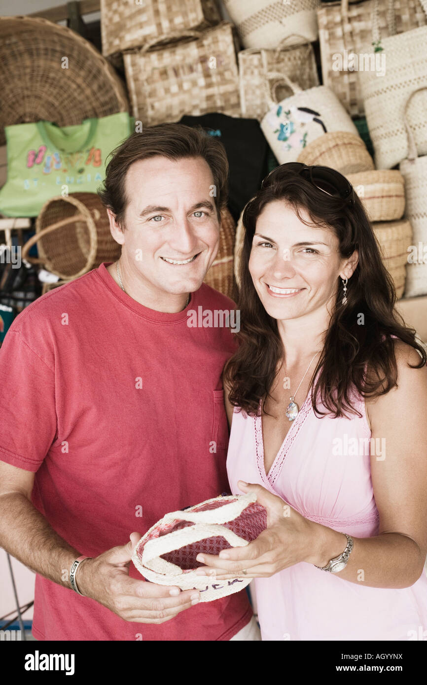 Portrait of a mid adult couple holding a hand bag and smiling - Stock Image