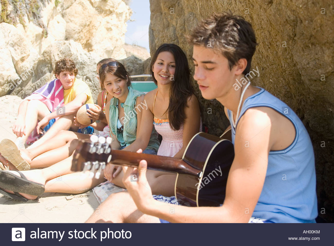 Teenage boy playing guitar for friends on beach Stock Photo