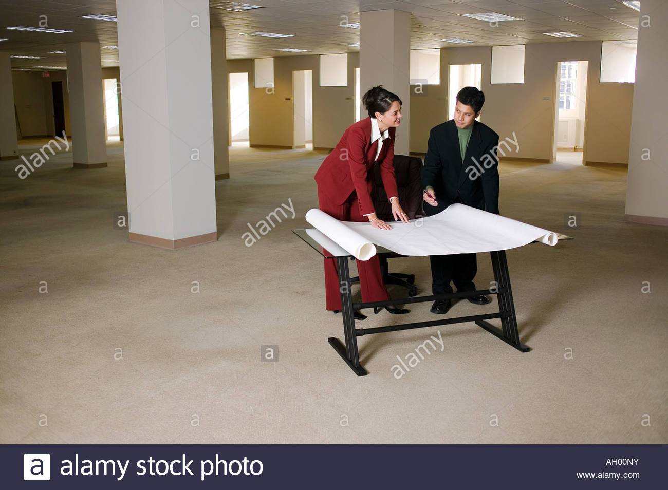Businesspeople looking at blueprints in empty office - Stock Image