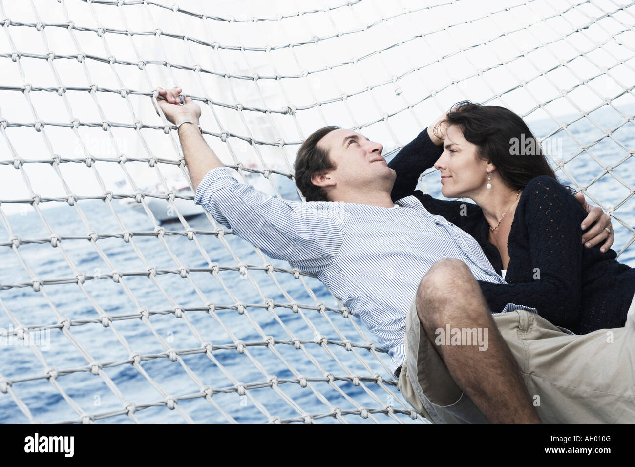 Mid adult couple lying in a hammock - Stock Image