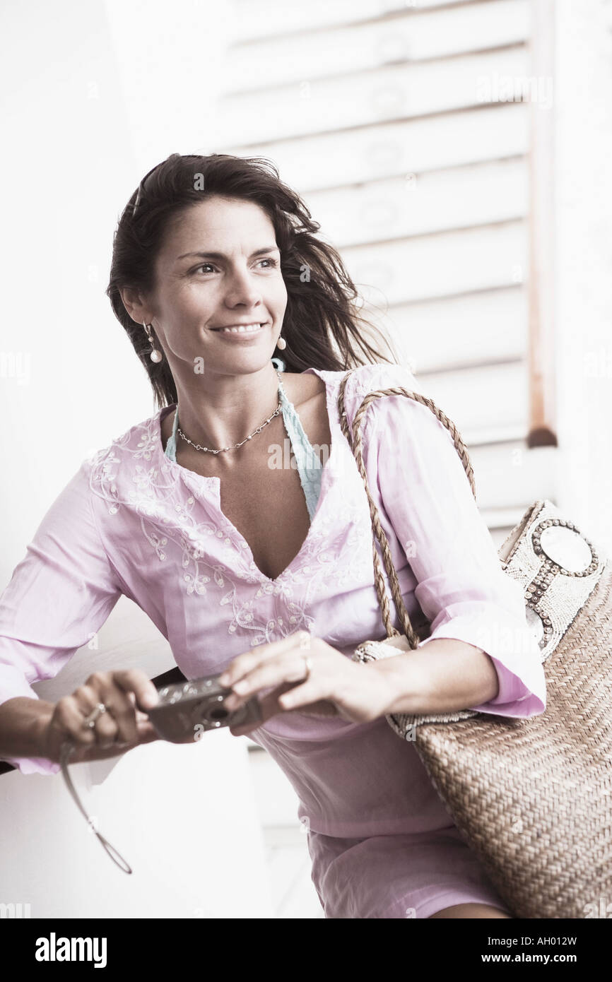 Close-up of a mid adult woman holding a digital camera and smiling Stock Photo