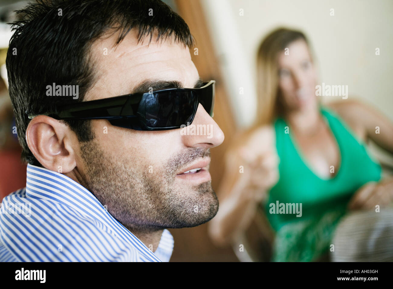 Close-up of a young man smiling with a mid adult woman sitting on a chair in the background - Stock Image