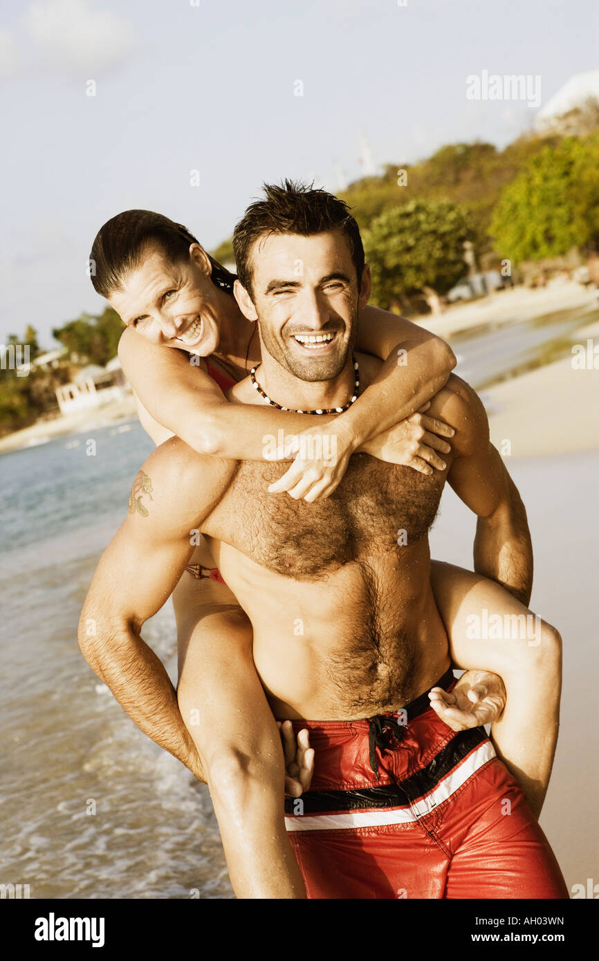 Mid adult man riding piggyback on a mid adult woman on the beach - Stock Image