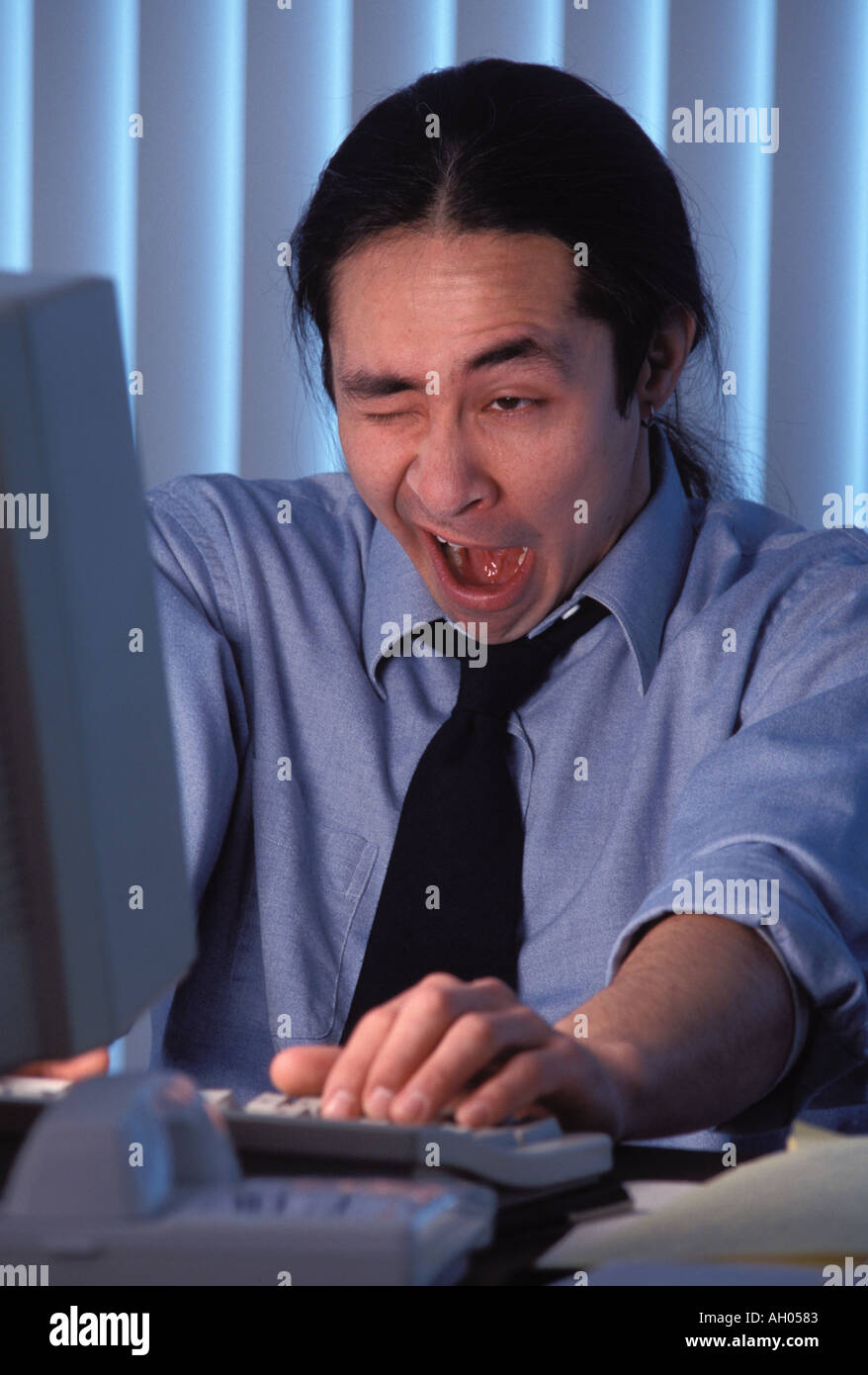 Sleepy Man Working Late at Office - Stock Image