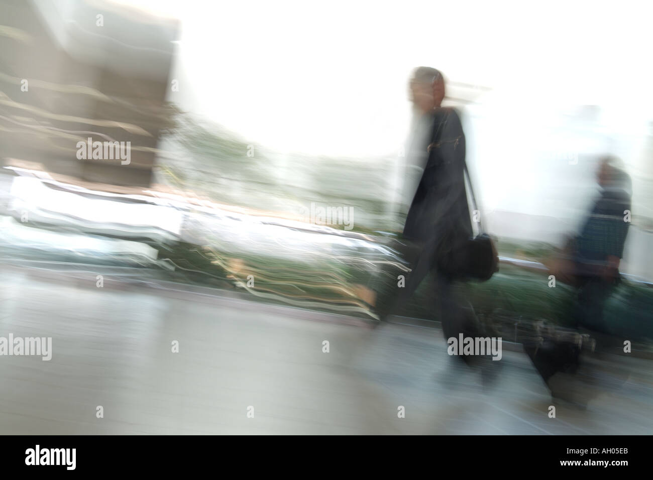 Late Businessman Traveller Walking Through Airport Quickly With Motion Blur - Stock Image