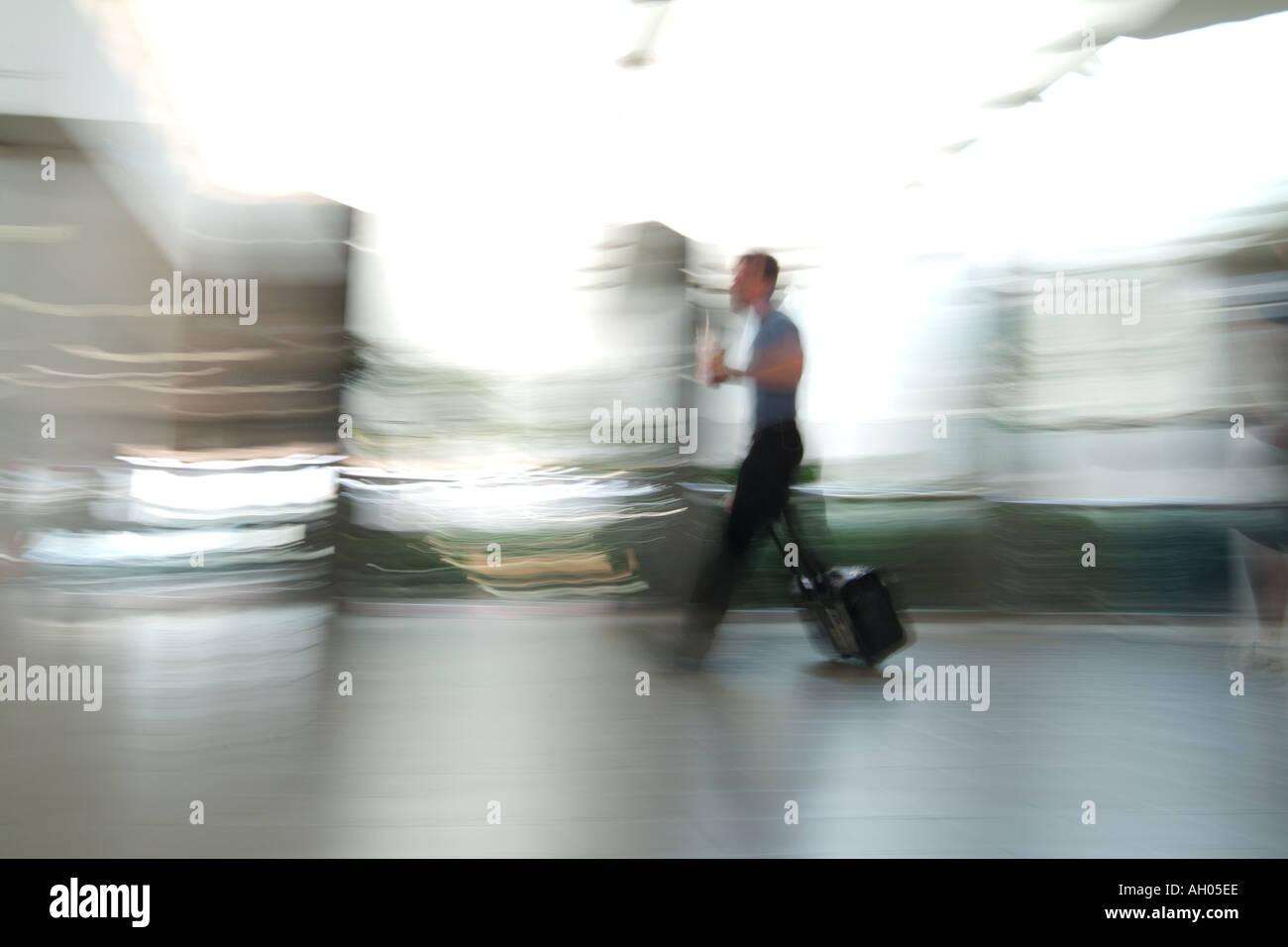 Late Businessman  Traveler Walking Through Airport Terminal Quickly - Stock Image