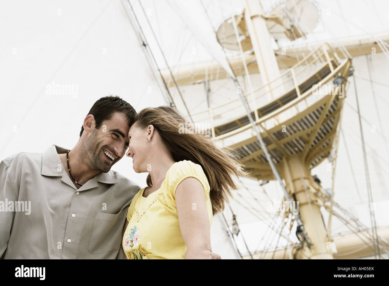 Low angle view of a mid adult couple on a sailing ship and smiling - Stock Image