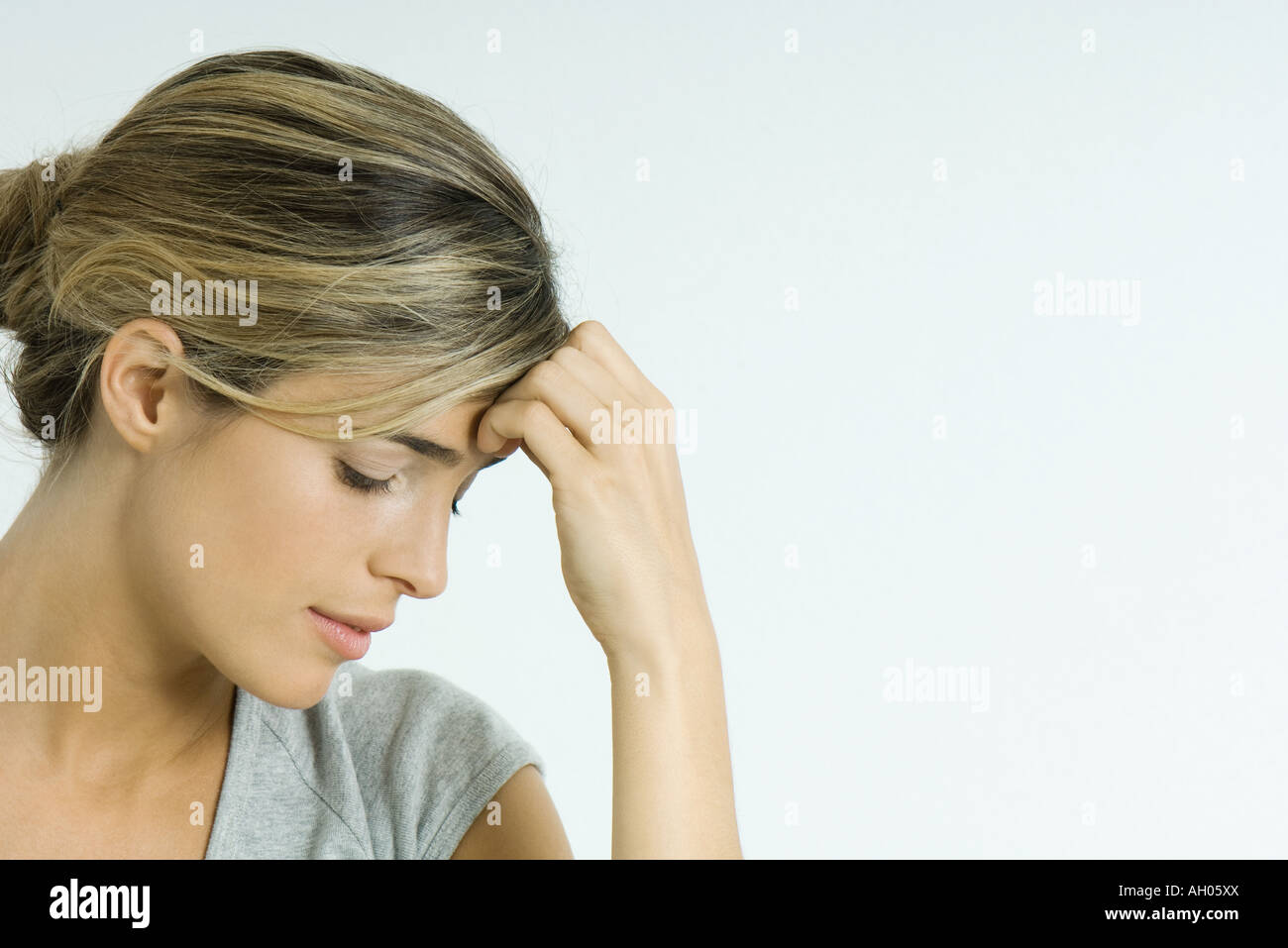 Young woman holding head, looking down, portrait - Stock Image